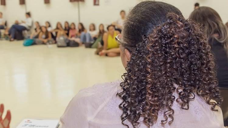 Ao fundo, grupo de pessoas sentadas no chão em roda. Mais próximo à câmera, de costas, uma mulher de cabelo cacheado preso.
