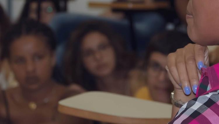 No fundo da imagem, desfocadas, três mulheres assistem o que outra, em foco, mais perto da câmera, fala.