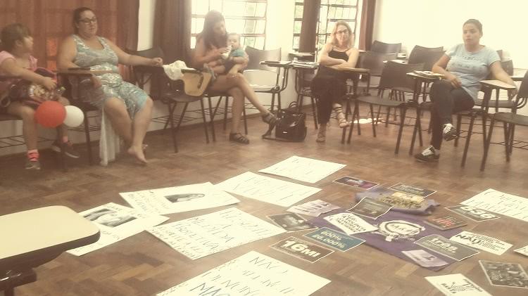 A foto mostra uma sala de aula, em que as cadeiras estão dispostas em círculo. Apenas parte do círculo aparece na foto, e há quatro mulheres e uma criança sentada. Uma das mulheres segura um bebê ao colo e oferece uma mamadeira. A criança é uma menina e segura dois balões enquanto olha para a mulher a seu lado. No chão, no que parece ser o centro do círculo feito com as cadeiras, há uma série de cartazes escritos à mão e outros com símbolos do feminismo. Não é possível ler o texto deles, pois a foto está ligeiramente desfocada.