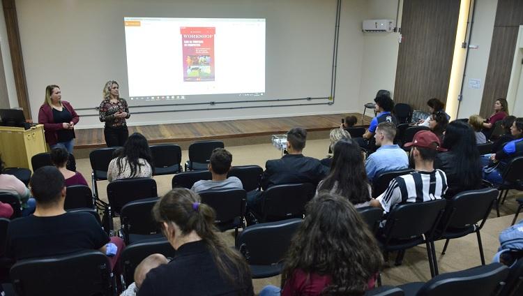 A foto mostra as organizadoras em frente a um projetor falando para uma plateia sentada em cadeiras em um auditório.