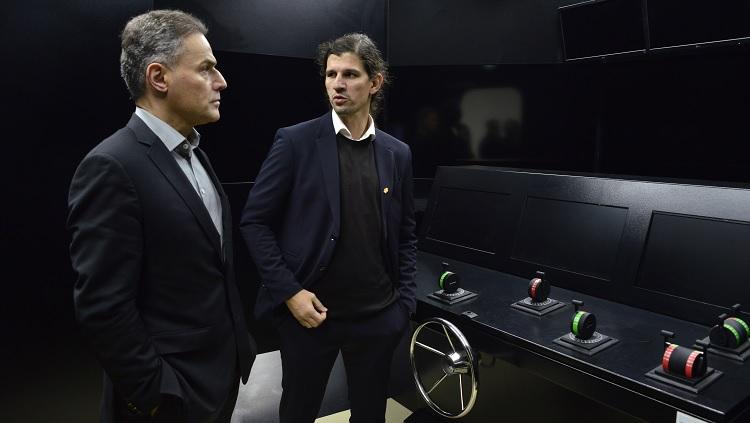 Em uma sala de simulação de embarcações navais, o diretor superintendente aparece ouvindo explicações do vice-reitor Danilo Giroldo.