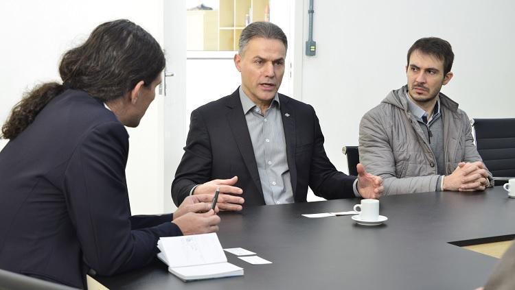 A foto mostra três homens em uma mesa de reuniões. O que está ao centro gesticula, enquanto os dois demais olham para ele.