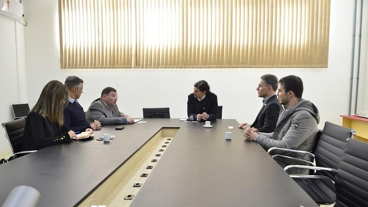 Em uma mesa de reuniões, aparecem seis pessoas, cinco homens e uma mulher.