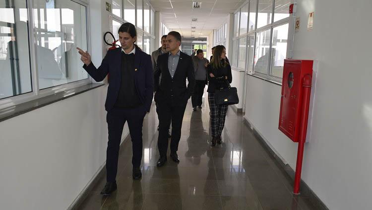 Uma comitiva caminho no corredor de um prédio. O homem que está à frente aponta para sua direita. Os demais o seguem.