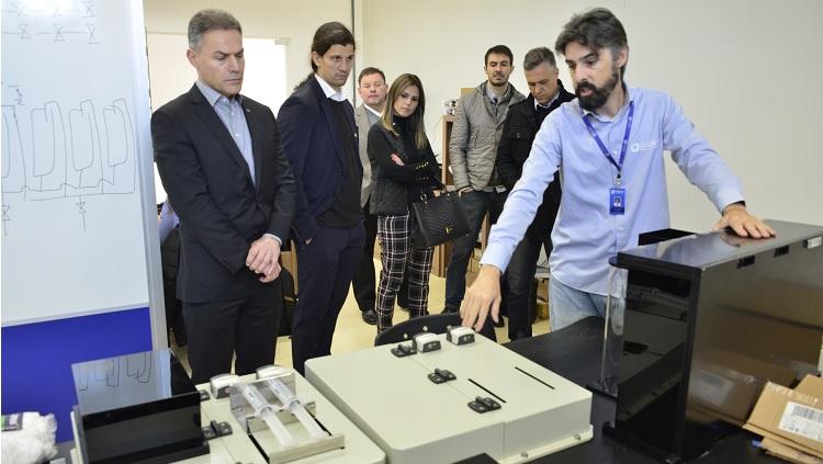 Os seis integrantes da comitiva assistem a explicações sobre equipamentos em uma sala, feitas por um homem que usa um crachá.