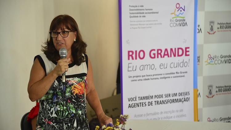 Reitora Cleuza aparece à esquerda na imagem, com o microfone na mão. À direita da foto, um banner, em que se lê o texto: Rio Grande: eu amo, eu cuido.