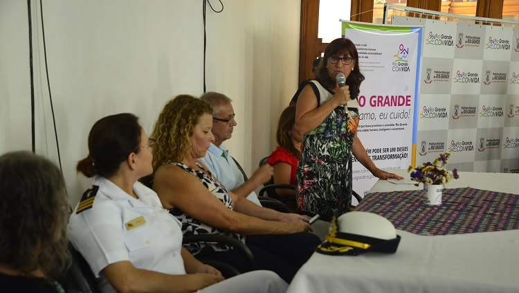 Em uma mesa, da direita para a esquerda, aparecem sentadas a representante da Marinha, a presidente da Câmara de Vereadores e o vice-prefeito de Rio Grande. Em pé, a reitora da Furg, com o microfone à mão.