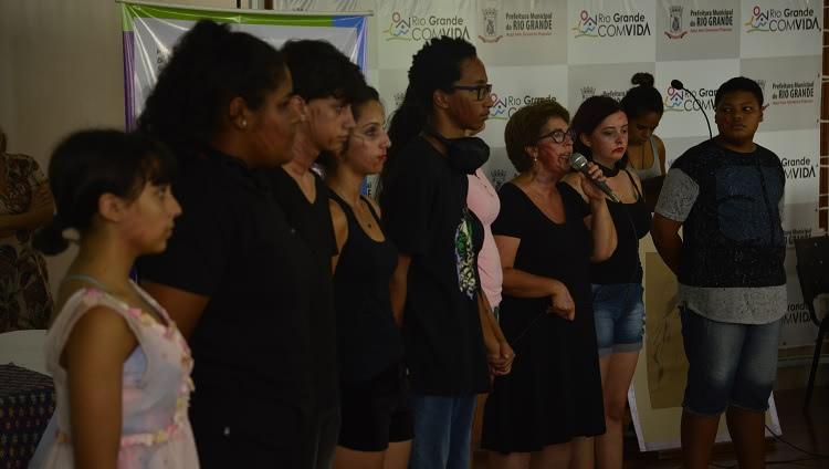 A imagem mostra os integrantes do grupo de teatro dispostos lado a lado. São dez pessoas. Uma delas, uma mulher, está com o microfone à mão e aparece falando.