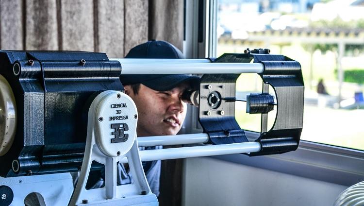 Imagem mostra visitante utilizando equipamento confeccionado pela impressora 3d da universidade