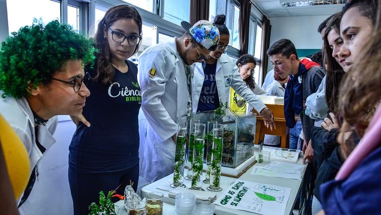 Imagem mostra estudantes da universidade apresentando equipamentos de laboratório