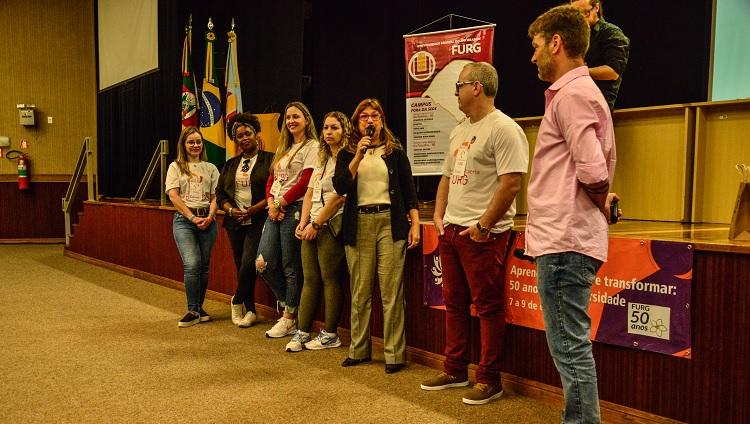 Imagem mostra servidores da universidade perfilados em frente ao palco do Cidec-Sul