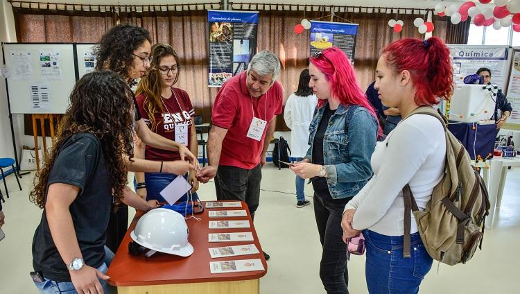 Imagem mostra visitantes conversando com estudantes apresentadores
