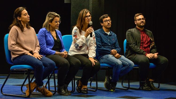 Mauren, idealizadora do projeto, aparece na foto em meio ao seu discurso, sentada segurando o microfone enquanto os demais componentes da mesa estão sentados ao seu lado.