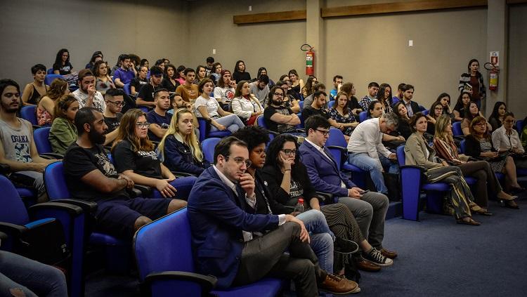 Imagem mostra várias pessoas sentadas nas cadeiras do auditório