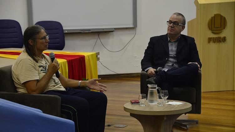 A imagem mostra duas pessoas, sentadas em poltronas, em um palco. Uma delas, Lucia Anello, fala ao microfone. O outro, Renato Duro Dias, olha para ela. À frente deles, há uma mesa de centro, com jarra e copos com água. Ao fundo, um púlpito onde se lê o nome da universidade: FURG.
