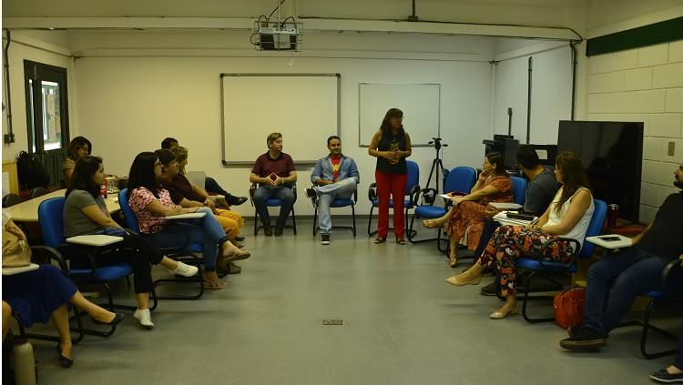 Em uma sala de aula, um grupo de 14 pessoas aparece sentado, em círculo. A reitora, professora Cleuza, está em pé, falando.