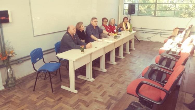 Na foto, os palestrantes da reunião estão sentados diante de uma mesa discursando para o público