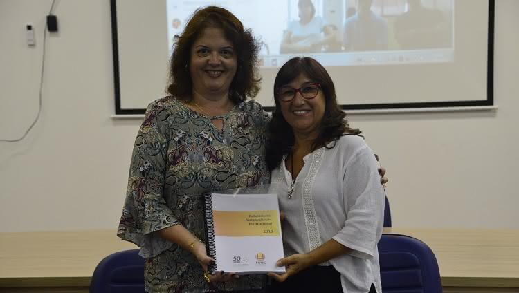 A imagem mostra a presidente da CPA Adriana Kivanski de Senna fazendo a entrega do Relatório de Avaliação Institucional 2018 para a reitora Cleuza Maria Sobral Dias