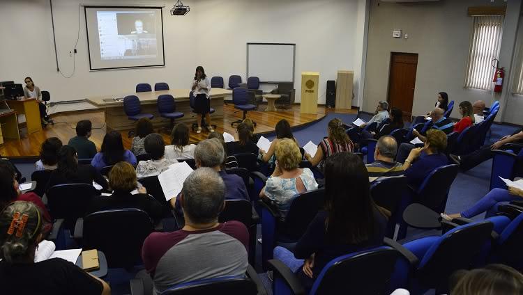 Em uma foto que mostra um auditório, o público aparece de costas. Ao fundo da imagem, no palco, a reitora Cleuza Maria Sobral Dias fala ao microfone.