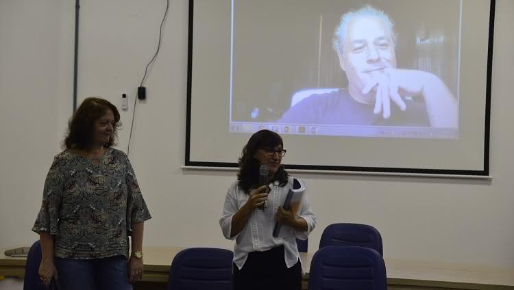 A presidente da CPA, Adriana Kivanski, e a reitora da FURG, Cleuza Maria Sobral Dias aparecem na foto. Elas estão no palco. Cleuza está com o microfone em uma mão e o relatório de avaliação institucional em outra. Atrás delas, em um telão, aparece um homem, que participa da reunião por teleconferência.