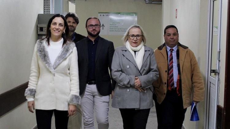 Cinco pessoas aparecem caminhando em um corredor hospitalar. São duas mulheres e três homens.