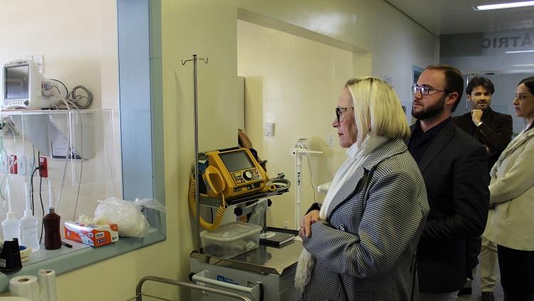 Na foto, a secretária de saúde olha para uma área assistencial. Atrás dela, estão outras três pessoas.