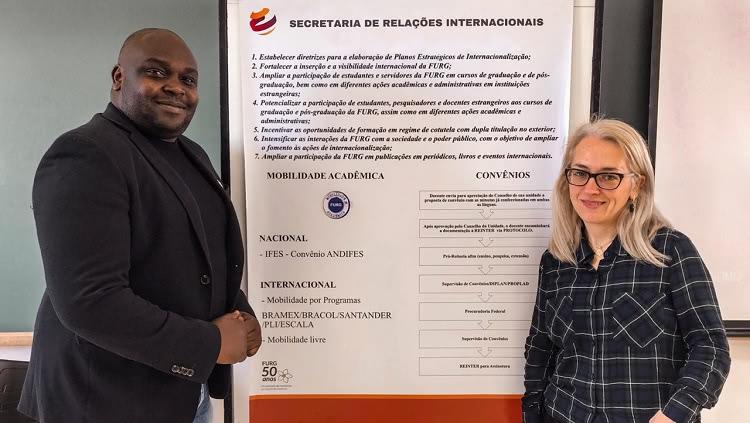Imagem mostra dois servidores da secretaria ao lado de banner de apresentação