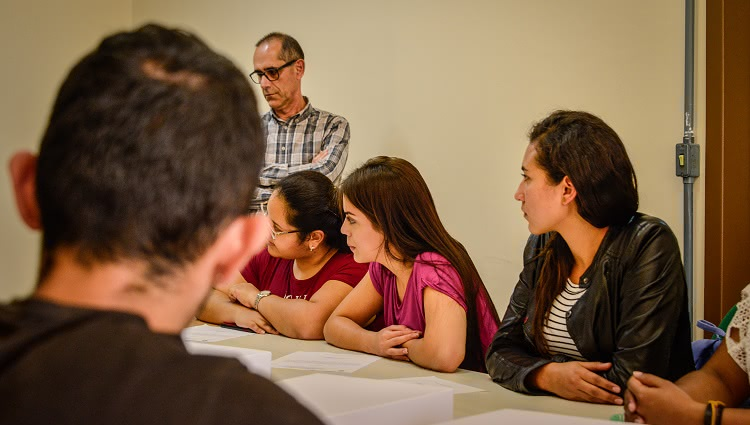 Imagem destaca estudantes reunidos ao redor de uma mesa