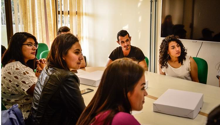 Imagem mostra estudantes reunidos ao redor de uma mesa