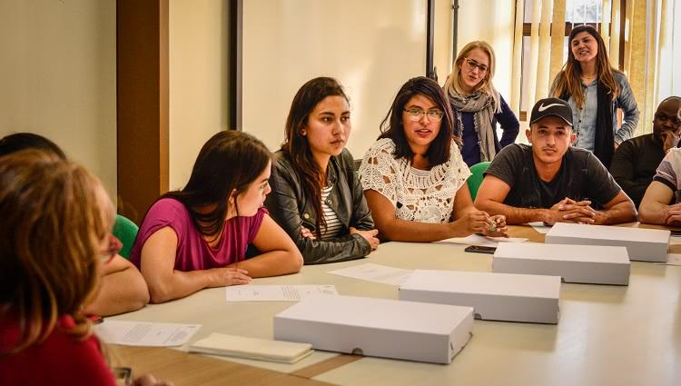 Imagem mostra estudantes internacionais ao redor de uma mesa
