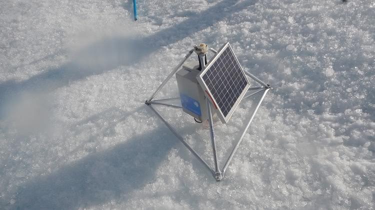Na imagem, um tripé de metal sobre uma superfície de gelo, com uma placa de luz solar