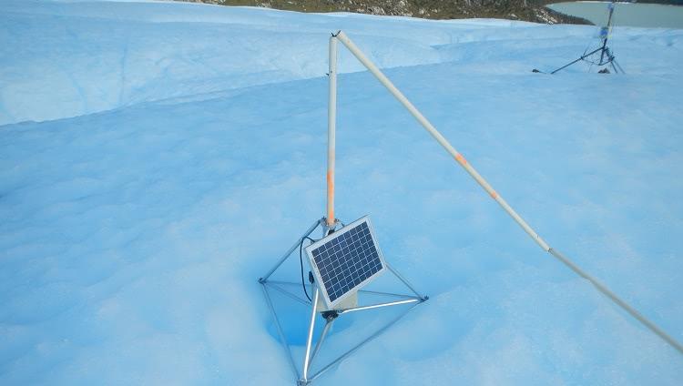 Sobre uma superfície de gelo, aparece um tripé de metal com um painel de luz solar. No centro dele, há segmentos de metal, que se desdobram no chão, como hastes de barracas