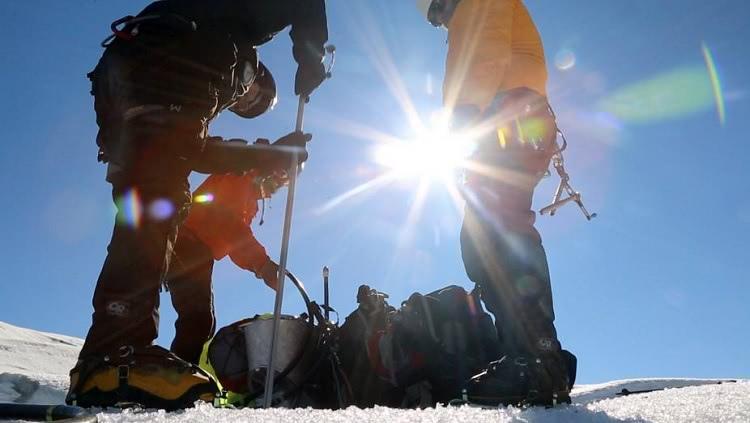 Contra a luz, três pessoas bem agasalhadas, inserem uma haste de PVC na geleira. No chão, próxima delas, há mochilas.