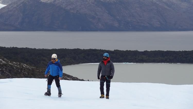 Dois homens agasalhados, com calçados com garras para neve, caminham sobre o gelo. Eles também usam capacete. Ao fundo deles se vêem um lago e, mais atrás, montanhas