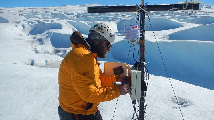 Um homem com bastante agasalhos e um capacete, aparece mexendo em um equipamento. Ao redor e ao fundo da imagem, há apenas gelo. Ele está sobre uma geleira.