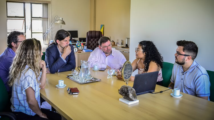 Imagem mostra seis pessoas, duas mulheres e quatro homens ao redor de uma mesa de reuniões. No centro, um notebook, usado para uma apresentação de slides. Os semblantes revelam interesse por parte dos rostos que estão virados para uma das mulheres, que, em contrapartida, assume postura de quem está comunicando sobre algo