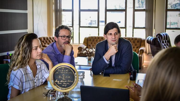 A imagem mostra em detalhe três pessoas, dois homens e uma mulher, eles estão com um semblante de total atenção