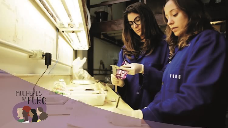 """Em um laboratório duas jovens mulheres aparecem trabalhando. Uma delas é Ana Luzia. Ambas usam jalecos azuis em que consta a inscrição """"Furg""""."""