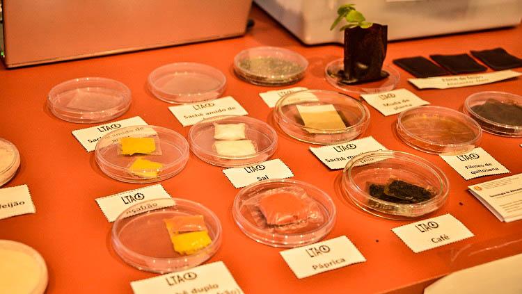 Pequenos recipientes de redondos de vidro estão sobre uma mesa. Dentro dos recipientes há pequenos saches envoltos em filme transparente. Os saches contém, conforme indicam pequenos pedaços de papel, açafrão, páprica, café, amido de milho, sal.