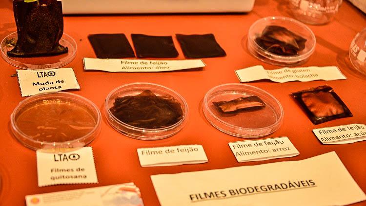 A imagem mostra outros filmes de origem orgânica. Eles aparecem em pequenos discos de vidro sobre uma mesa. Em pedaços de papel a indicação de que são feitos de feijão e de quitosana.