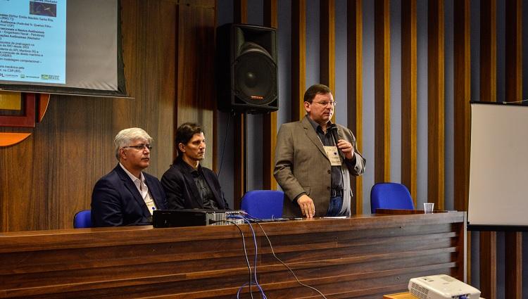 Imagem mostra três homens, sendo um deles em pé e em posse do microfone, atrás de uma bancada