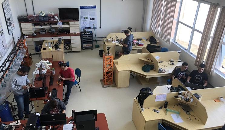 A imagem mostra uma sala com mesas de trabalho dispostas lado a lado. Na lateral tem janelas. Ao fundo uma mesa com computador.