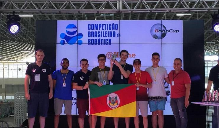 A foto mostra alunos integrantes do Nautec recebendo um prêmio por um trabalho apresentado. O grupo segura o troféu e também a bandeira do Rio Grande do Sul.