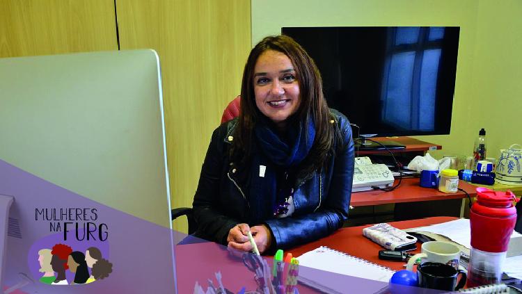 Na imagem, uma mulher aparece sentada atrás de uma mesa, na qual há uma computador. Ela olha para a foto e sorri. Sobre a mesa há um caderno, canetas, xícaras, telefone e outros materiais. Atrás dela, um armário de escritório e, sobre outra mesa, uma TV e um aparelho de telefone