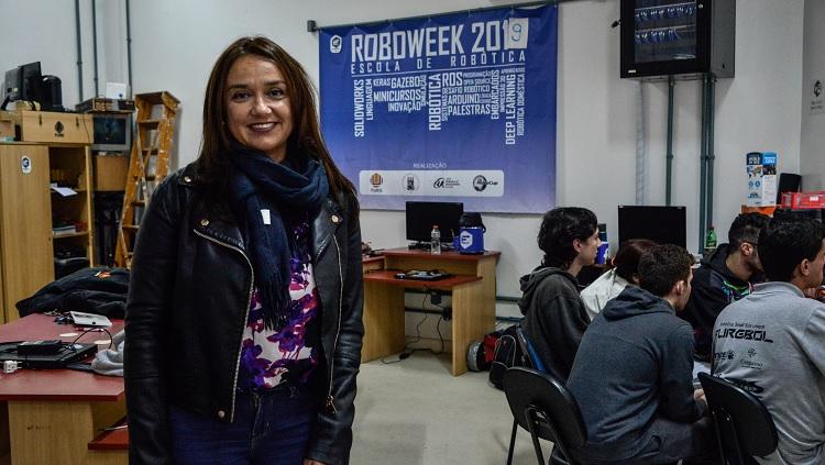 Em primeiro plano, aparece uma mulher em pé em uma ampla sala de aula. Ao fundo, na parede, há um banner, em que está escrito Roboweek 2019 - escola de robótica. Há mesas e cadeiras ao fundo. Cerca de 5 estudantes aparecem sentados em uma mesa, de costas para a imagem.