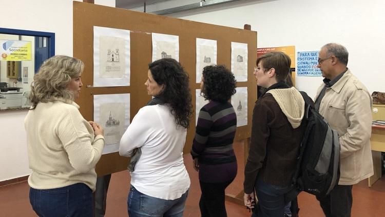 A foto mostra um grupo de pessoas virado para um painel onde estão expostos os desenhos do professor Antônio Valente.