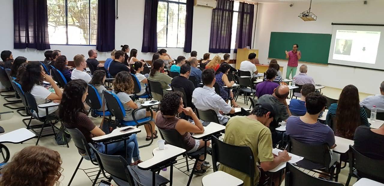 A foto mostra uma sala de aula cheia. Na frente da turma, um professor fala aos alunos com uma projeção ao fundo.