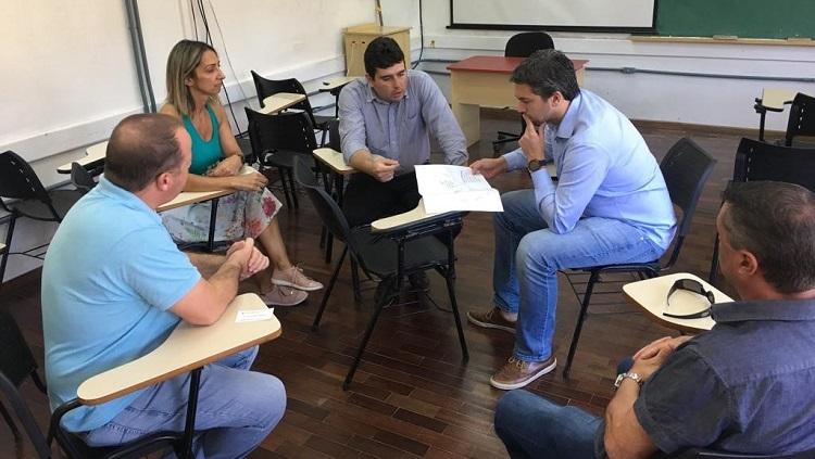 Em uma sala de aula, estão sentados em círculo, quatro homens e uma mulher. Dois deles se detém sobre um documento.