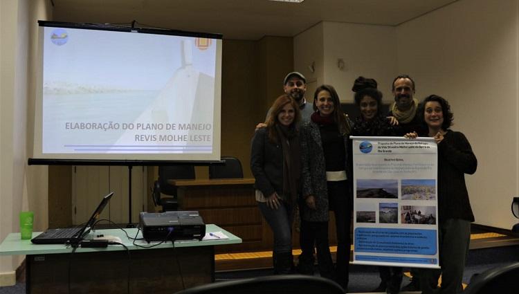 Em frente a uma projeção, a equipe de pesquisadores segura um cartaz com dados sobre o projeto
