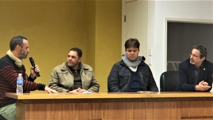 Quatro homens sentados lado a lado em uma mesa enquanto um deles segura o microfone